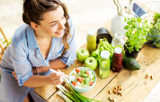 smiling pretty woman eating a salad she made at home - healthy eating