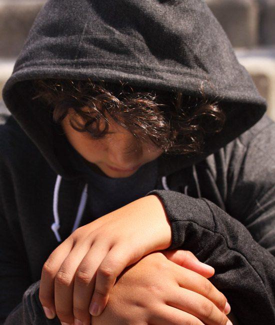 sad young teenage boy in black hoodie looking down