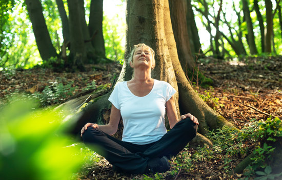 blonde older woman sitting cross-legged outdoors in the forest - ecotherapy