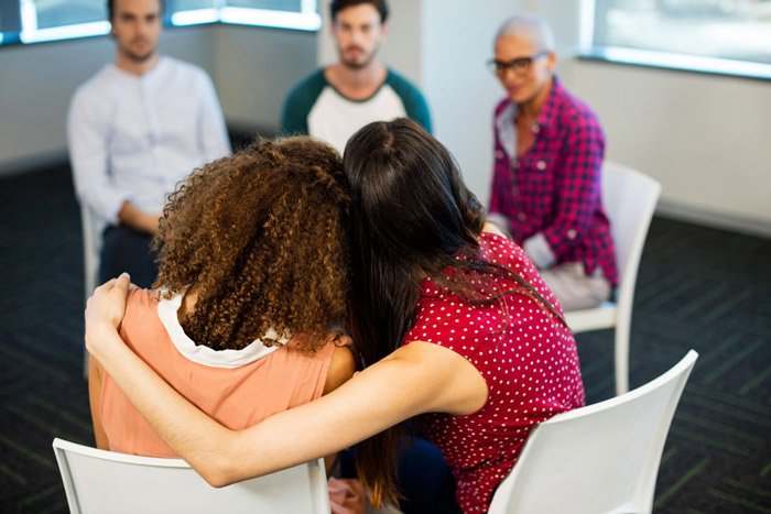 woman side-hugging another woman during a group therapy session