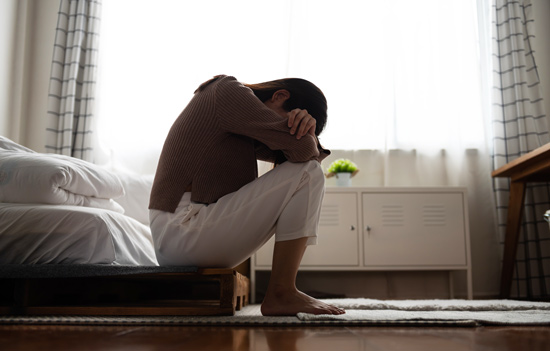 woman sitting on the edge of her bed with her head down in her arms - PTSD