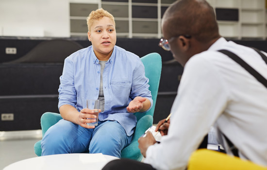 woman speaking to her psychologist or therapist during a session - depression