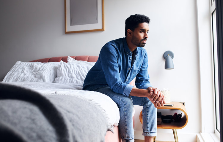 handsome man in his early thirties sitting on the edge of his bed thinking - adjustment disorder
