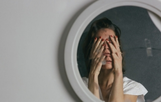 reflection of woman covering her face with her hands; the mirror is cracked making part of her reflection doubled - co-occurring diagnoses
