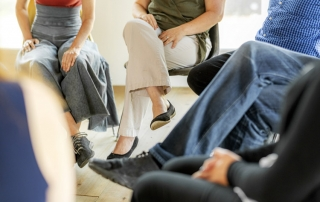 cropped shot of group of people sitting in chairs in a circle - group therapy - CBT